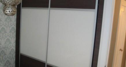 Armario con puertas correderas en formica y cristal lacado.